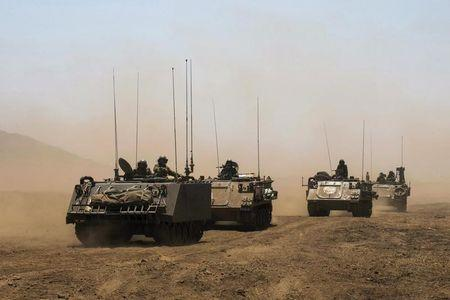 Israeli soldiers ride armoured vehicles during an exercise in the Israeli-occupied Golan Heights