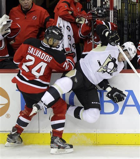New Jersey Devils' Bryce Salvador (24) checks Pittsburgh Penguins' James Neal during the third period of an NHL hockey game on Sunday, Feb. 5, 2012, in Newark, N.J. The Devils won 5-2. (AP Photo/Julio Cortez)