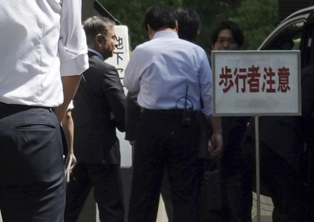Former Nissan chairman Carlos Ghosn, second from left, arrives at Tokyo District Court for a pre-trial meeting Thursday, May 23, 2019, in Tokyo. Ghosn, who is out on bail, has been charged with under-reporting his post-retirement compensation and breach of trust in diverting Nissan money and allegedly having it shoulder his personal investment losses. (AP Photo/Eugene Hoshiko)