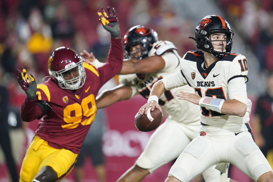 Oregon State quarterback Chance Nolan, right, throws as Southern California linebacker Drake Jackson (99) closes in during the first half of an NCAA college football game Saturday, Sept. 25, 2021, in Los Angeles. (AP Photo/Marcio Jose Sanchez)