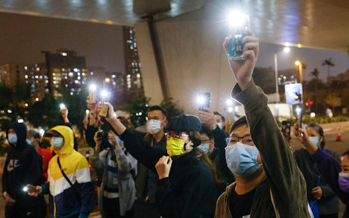 Supporters of 47 pro-democracy activists hold flashlights as they wait for four of them to leave the West Kowloon Magistrates Courts on bail - Tyrone Siu/Reuters