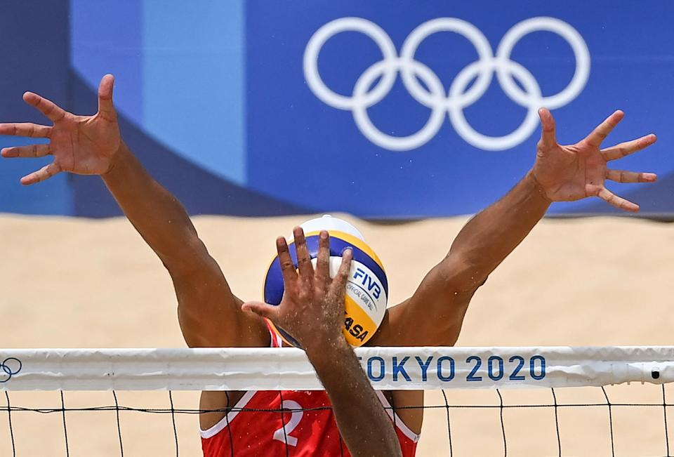 <p>Russia's Oleg Stoyanovskiy (red) blocks a shot by Mexico's Josue Gaston Gaxiola Leyva in the men's preliminary beach volleyball Pool B match between Russia and Mexico at Shiokaze Park.</p>