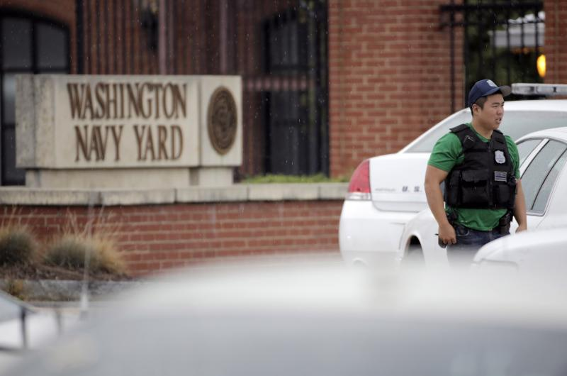 A law enforcement officer keeps bystanders back from the scene of a shooting at the Washington Navy Yard in Washington