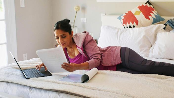 A mature aged woman working with a laptop computer in the bedroom of her suburban home in Los Angeles California USA.