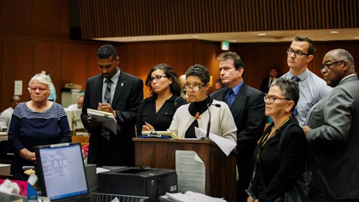 """Social workers Patricia Clement, left, and Stefanie Rodriguez, third from left, and supervisors Kevin Bom, second from right, and Gregory Merritt, fourth from right, who were charged with child abuse in the death of 8-year-old Gabriel Fernandez, appear with their lawyers at their arraignment in 2016. <span class=""""copyright"""">(Los Angeles Times)</span>"""