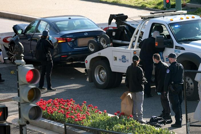 A tow truck removes a car as law enforcement collect evidence at the scene after a vehicle charged a barricade