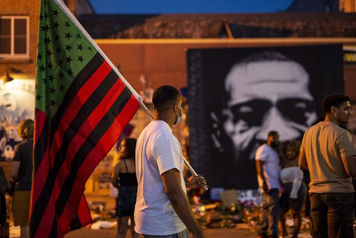 A man carries a Black Liberation flag through a Juneteenth celebration at a memorial for George Floyd outside Cup Foods on June 19, 2020 in Minneapolis.