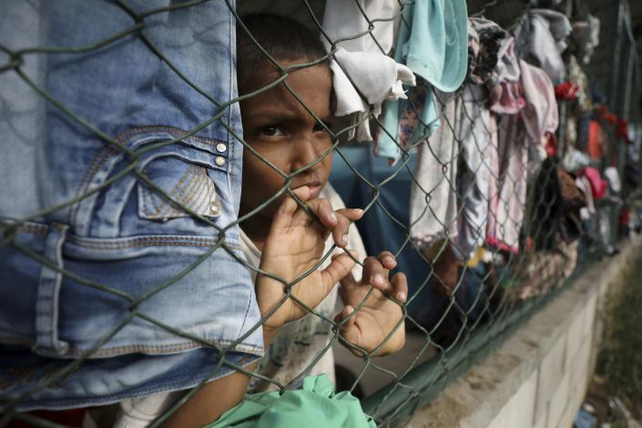 A child looks through a fence of a shelter at a community center in Arauquita, Colombia, Thursday, March 25, 2021, on the border with Venezuela. Thousands of Venezuelans are seeking shelter in Colombia this week following clashes between Venezuela's military and a Colombian armed group in a community along the nations' shared border. (AP Photo/Fernando Vergara)