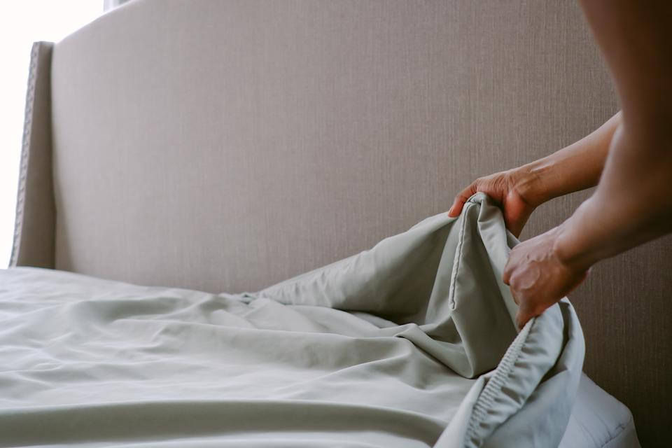 Close-up of unrecognizable woman putting freshly laundered sheet on bed