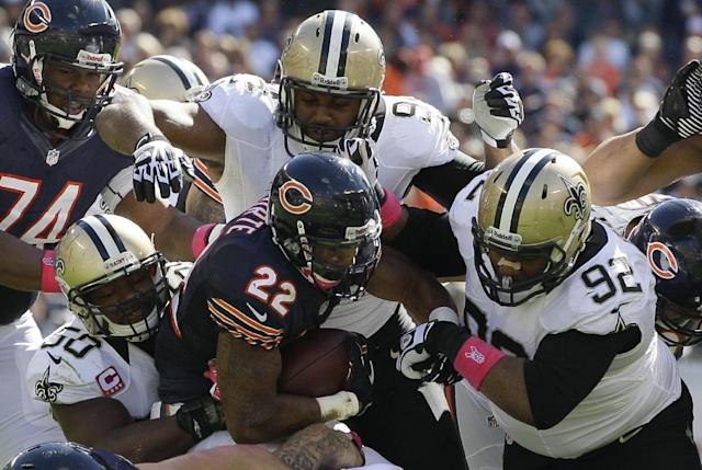 Chicago Bears running back Matt Forte (22) gets tackled by New Orleans Saints middle linebacker Curtis Lofton (50), defensive end Cameron Jordan (94) and nose tackle John Jenkins (92) during the first half of an NFL football game, Sunday, Oct. 6, 2013, in Chicago.(AP Photo/Nam Y. Huh)