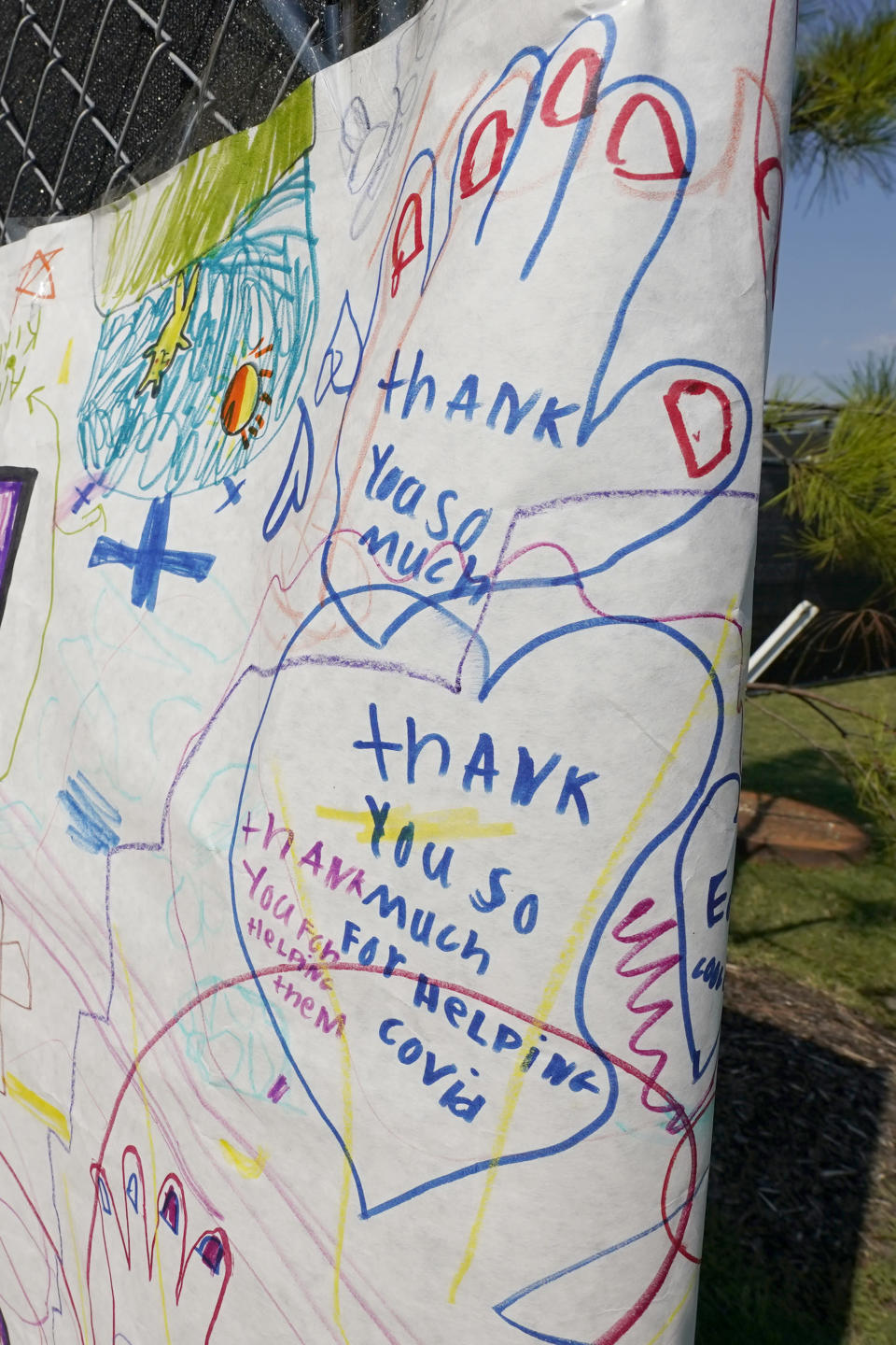 An oversized poster, drawn by the school children of an area Christian school thanking the medical workers with both Samaritan's Purse Missions and the University of Mississippi Medical Center, decorates the entrance leading to a field hospital based in a covered parking lot at the medical facility, in Jackson, Miss., Wednesday, Aug. 25, 2021. (AP Photo/Rogelio V. Solis)