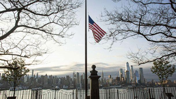 PHOTO: Flags are flying at half-mast as the sun rises behind in Manhattan, April 6, 2020, from Weehawken, New Jersey. (Kena Betancur/Getty Images)