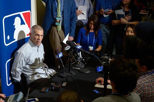 New York Yankees manager Joe Girardi, left, answers a question from reporters during a media availability at baseball's winter meetings in Lake Buena Vista, Fla., Tuesday, Dec. 10, 2013.(AP Photo/Phelan M. Ebenhack)