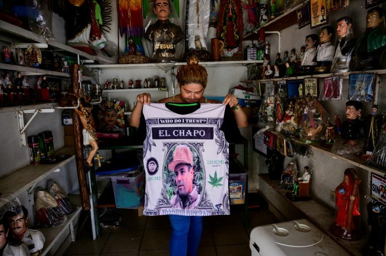 "A vendor shows a shirt featuring a portrait of drug lord Joaquin ""El Chapo"" Guzman, whom many residents of Mexico's Sinaloa view as a benefactor of the region (AFP Photo/Pedro PARDO)"