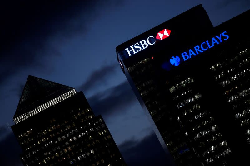 FILE PHOTO: HSBC and Barclay's buildings are lit up at dusk in the Canary Wharf financial district of London