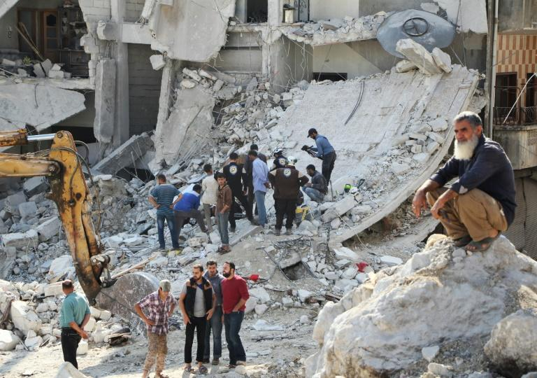 Syrian civil defence volunteers (C) search for victims amid the rubble of destroyed buildings on October 24, 2016, following overnight air strikes in the rebel-held town of Kafar Takharim, in Idlib province of northwest Syria