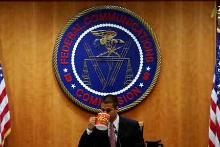 FILE PHOTO: Chairman Ajit Pai drinks coffee ahead of the vote on the repeal of so called net neutrality rules at the Federal Communications Commission in Washington, U.S., December 14, 2017. REUTERS/Aaron P. Bernstein/File Photo