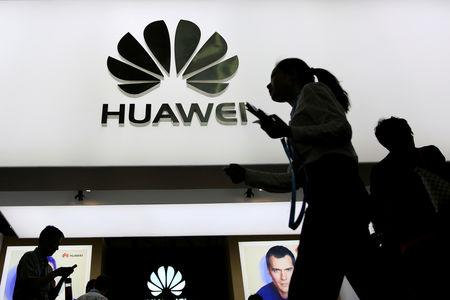 People walk past a sign board of Huawei at CES (Consumer Electronics Show) Asia 2016 in Shanghai, China May 12, 2016. REUTERS/Aly Song/File Photo