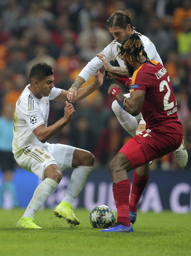 Galatasaray's Christian Luyindama, right, duels for the ball with Real Madrid's Casemiro, left, and Real Madrid's Sergio Ramos during the Champions League group A soccer match between Galatasaray and Real Madrid in Istanbul, Tuesday, Oct. 22, 2019. (AP Photo)