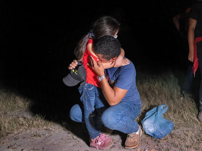 A light shines on a father, crouched down, hugging his daughter at nighttime.