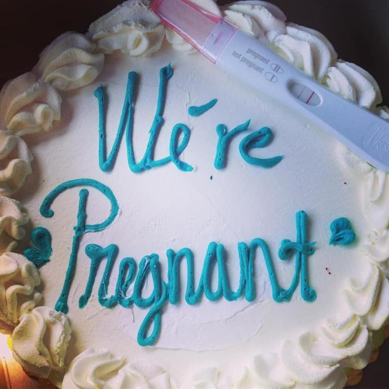 A cake announcing a pregnancy with a positive pregnancy test on it.