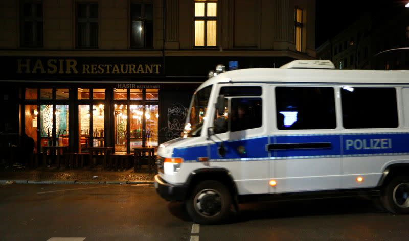A police car drives in front of a closed restaurant is pictured during the late-night curfew due to restrictions against the spread of the coronavirus disease (COVID-19) in Berlin
