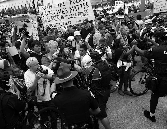 <p>An Akron police officer uses his bicycle to push journalists and anti-Trump demonstrators away from members of the Bible Believers group. (Photo: Khue Bui for Yahoo News)</p>