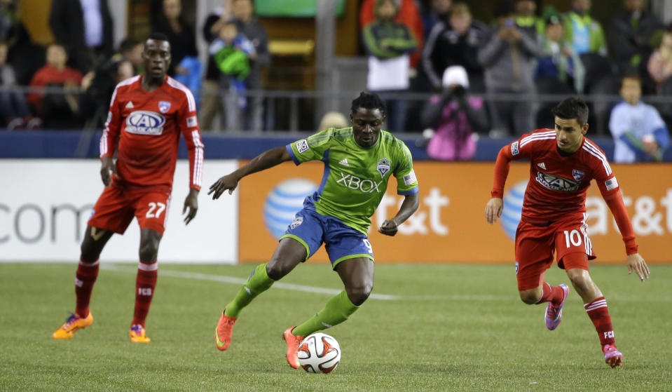 Seattle Sounders' Obafemi Martins, center, dribbles against FC Dallas' Mauro Diaz, right, in the first half of an MLS western conference semifinal soccer match, Monday, Nov. 10, 2014, in Seattle. (AP Photo/Ted S. Warren)