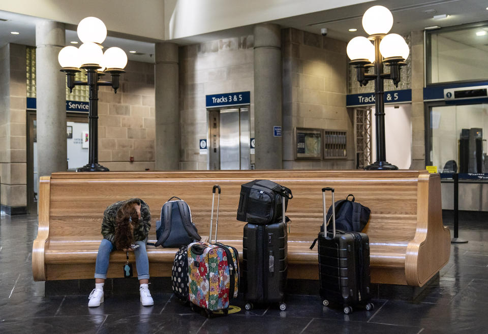 A passenger waits to board a train at the station in Providence, R.I., Friday, Nov. 20, 2020. With the coronavirus surging out of control, the nation's top public health agency pleaded with Americans not to travel for Thanksgiving and not to spend the holiday with people from outside their household. (AP Photo/David Goldman)
