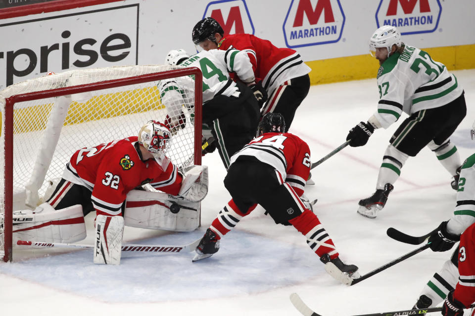 Chicago Blackhawks goaltender Kevin Lankinen (32) stops the shot of Dallas Stars center Justin Dowling (37) during the second period of an NHL hockey game Tuesday, April 6, 2021, in Chicago. (AP Photo/Jeff Haynes)