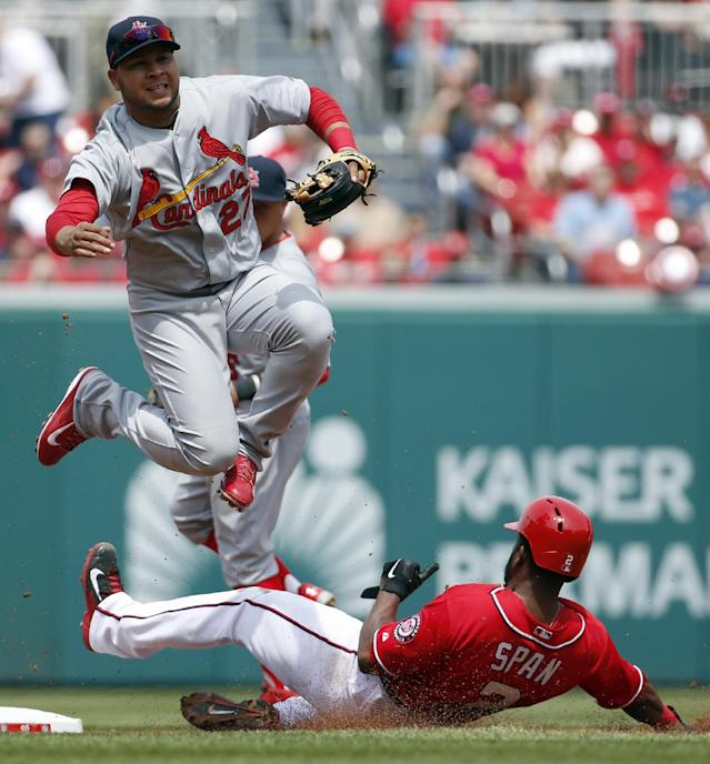 St. Louis Cardinals shortstop Jhonny Peralta jumps over Washington Nationals' Denard Span at second base, watching his throw to first to complete a double play on Bryce Harper during the first inning of a baseball game at Nationals Park on Saturday, April 19, 2014, in Washington. (AP Photo/Alex Brandon)