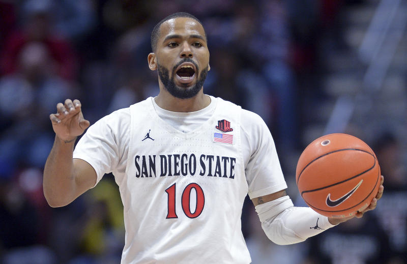 FILE - In this Dec. 28, 2019, file photo, San Diego State guard KJ Feagin gestures as he dribbles the ball during the second half of an NCAA college basketball game against Cal Poly in San Diego. It's almost like coach Brian Dutcher and the San Diego State Aztecs won the lottery. Tired of losing at their old schools, big man Yanni Wetzell and guards Malachi Flynn and Feagin transferred to San Diego State after being lured by the prospect of winning and going to the NCAA Tournament. And boy, have they ever won, to the point that they've matched some accomplishments by the breakthrough 2010-11 team led by the most famous player in program history, Kawhi Leonard. (AP Photo/Orlando Ramirez, File)