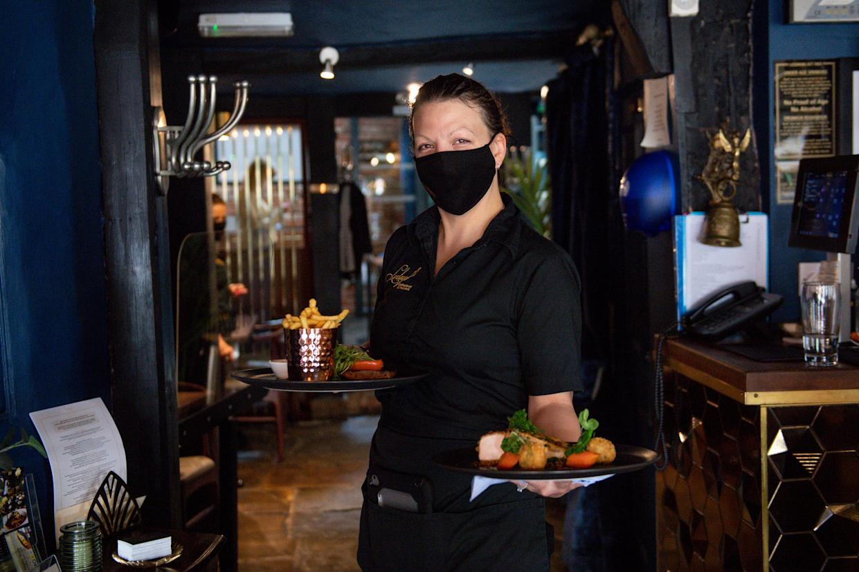 A waitress carries meals to a table during service at Loxleys Restaurant & Wine Bar in Stratford, Warwickshire, as indoor hospitality and entertainment venues reopen to the public following the further easing of lockdown restrictions in England. Picture date: Monday May 17, 2021. (Photo by Jacob King/PA Images via Getty Images)