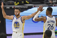 Golden State Warriors' Stephen Curry (30) and Kent Bazemore (26) celebrate before being substituted out of the game in the second half of an NBA basketball game against the Cleveland Cavaliers, Thursday, April 15, 2021, in Cleveland. The Warriors won 119-101. (AP Photo/David Dermer)