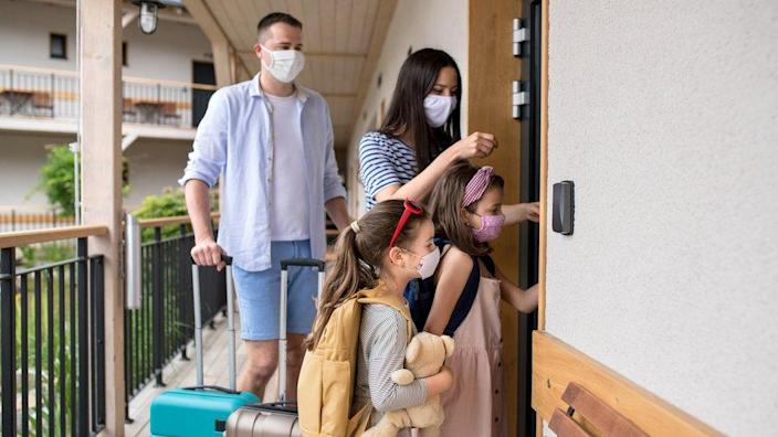 A family wearing face masks checks into a hotel