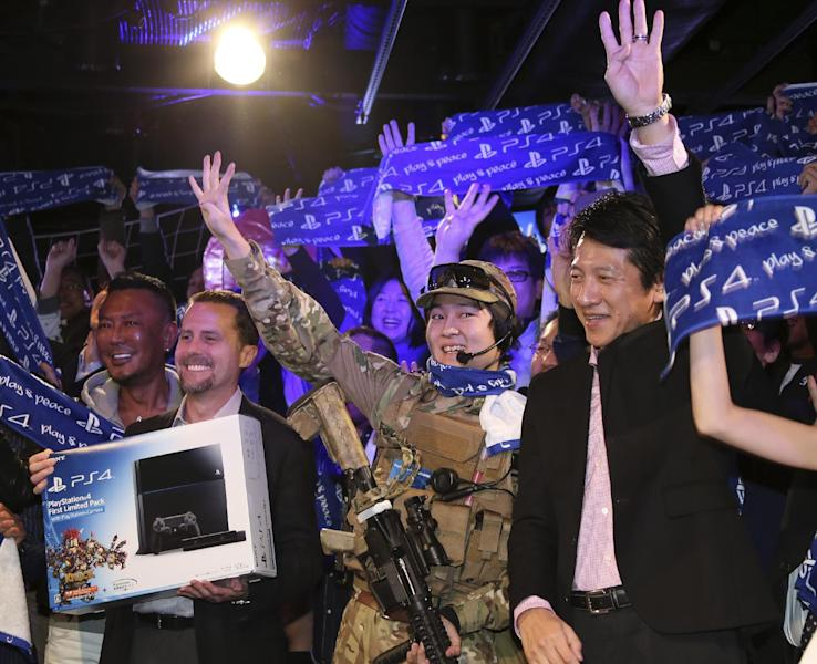 Sony Computer Entertainment Inc. President and CEO Andrew House, second left, Sony Computer Entertainment Japan President Hiroshi Kawano, right, and first customer of PlayStation 4 , center, pose for photo during launch event in Tokyo, Saturday, Feb. 22, 2014. (AP Photo/Koji Sasahara)