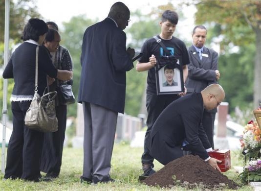 Di Rang Lin (2nd L), father of slain student Jun Lin, looks on as his son's ashes are laid to rest during funeral services in Montreal July 26, 2012.