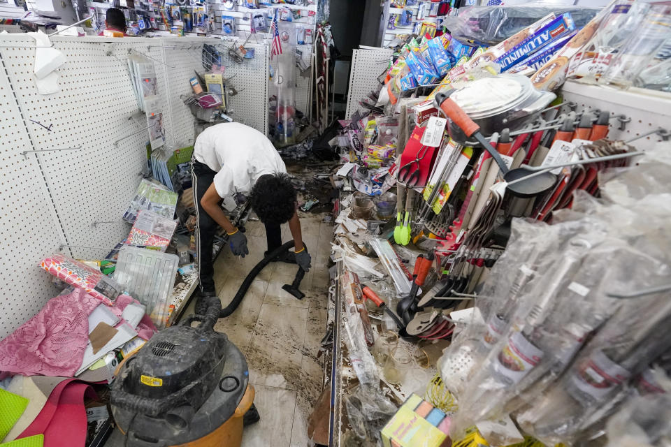 A worker uses a heavy duty vacuum cleaner to collect flood water off the floor of the Dollar Depot store after remnants of Hurricane Ida inundated the community, Saturday, Sept. 4, 2021, in Mamaroneck, N.Y. More than four days after the hurricane blew ashore in Louisiana, Ida's rainy remains hit the Northeast with stunning fury on Wednesday and Thursday, submerging cars, swamping subway stations and basement apartments and drowning scores of people in five states. (AP Photo/Mary Altaffer)