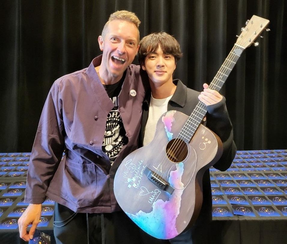 Jin (right) holding the guitar given to him by Chris Martin. — Picture via Twitter