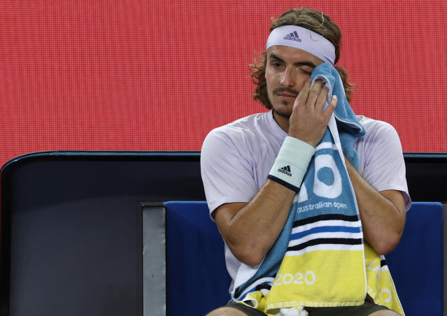Greece's Stefanos Tsitsipas wipes the sweat from his eye during a break in his third round singles match against Canada's Milos Raonic at the Australian Open tennis championship in Melbourne, Australia, Friday, Jan. 24, 2020. (AP Photo/Andy Wong)