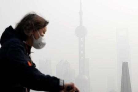 People walk on a bridge in front of the financial district of Pudong during a polluted day in Shanghai