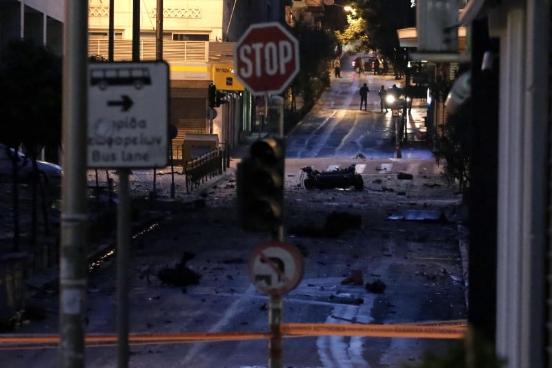 The remains of a car sit on a street after a car bomb explosion in central Athens, on Thursday, April 10, 2014. The bomb exploded outside a Bank of Greece building in central Athens before dawn Thursday, causing some damage but no injuries. The blast came hours before Greece was to return to the international bond markets for the first time in four years, and a day before German Chancellor Angela Merkel was to visit Athens.(AP Photo/ Petros Giannakouris)