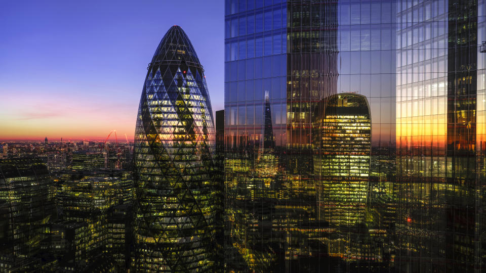 UK, London, digital composite of modern skyscrapers in the financial district viewed from high up, illuminated at dusk