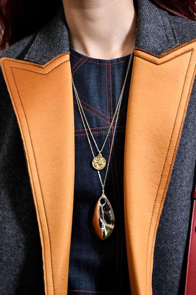 <p>Layered gold coin necklace and silver pendant necklace at the Tory Burch FW18 show. (Photo: Getty Images) </p>