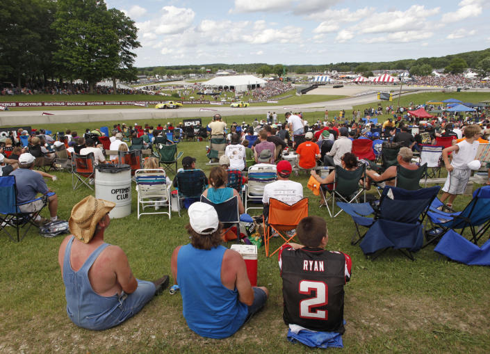 """FILE - Fans watch the Bucyrus 200 NASCAR Nationwide series race at Road America in Elkhart Lake, Wi., in this Saturday, June, 19, 2010, file photo. For all its history, Road America only hosted NASCAR's premier series once before, when Tim Flock won a rainy Grand National event back in 1956. That changes Sunday on the Fourth of July -- a coup for a facility that bills itself as """"America's national park for speed"""" but until this year couldn't land a Cup date. (AP Photo/Jeffrey Phelps, File)"""