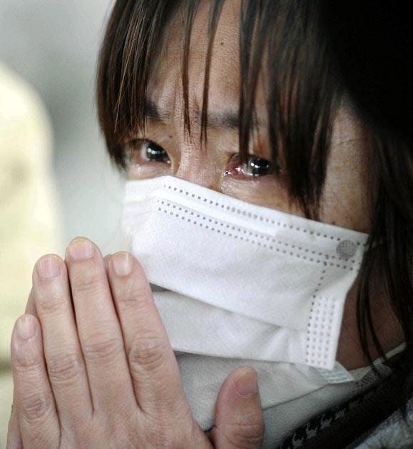 A woman reacts at the news of her relative's death in an evacuation shelter for survivors of Friday's earthquake and tsunami Tuesday, March 15, 2011, in Kesennuma, Miyagi Prefecture, Japan.  (AP Photo/Kyodo News)