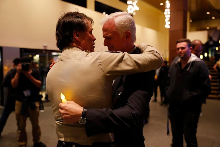 Thousand Oaks Police Chief Tim Hagel, left, hugs Officer Chris Dunn at the vigil. (Photo: Mike Blake / Reuters)