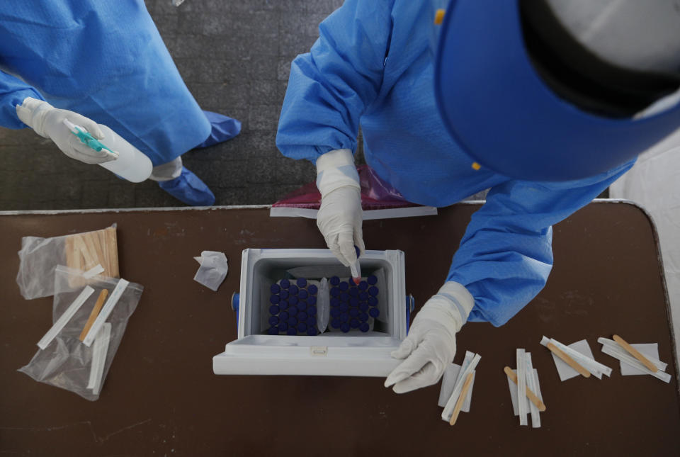Healthcare workers collect samples from new coronavirus tests inside a mobile diagnostic tent, in the Coyoacan district of Mexico City, Friday, Nov. 13, 2020. Mexico City announced Friday it will order bars closed for two weeks after the number of people hospitalized for COVID-19 rose to levels not seen since August. (AP Photo/Eduardo Verdugo)