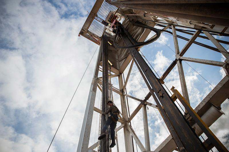 Jeff Allyn, a derrick hand with Raven Drilling, is lowered down from the top of a derrick while drilling for oil in the Bakken shale formation on July 23, 2013 outside Watford City, North Dakota. (Photo by Andrew Burton/Getty Images)