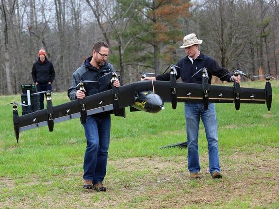 """NASA engineers David North (left) and Bill Fredericks (right) carry the """"Greased Lightning"""" drone before one of its flight tests."""